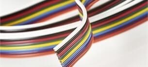 close up view of rainbow coloured ribbon cable wrapped in a circle on a white background